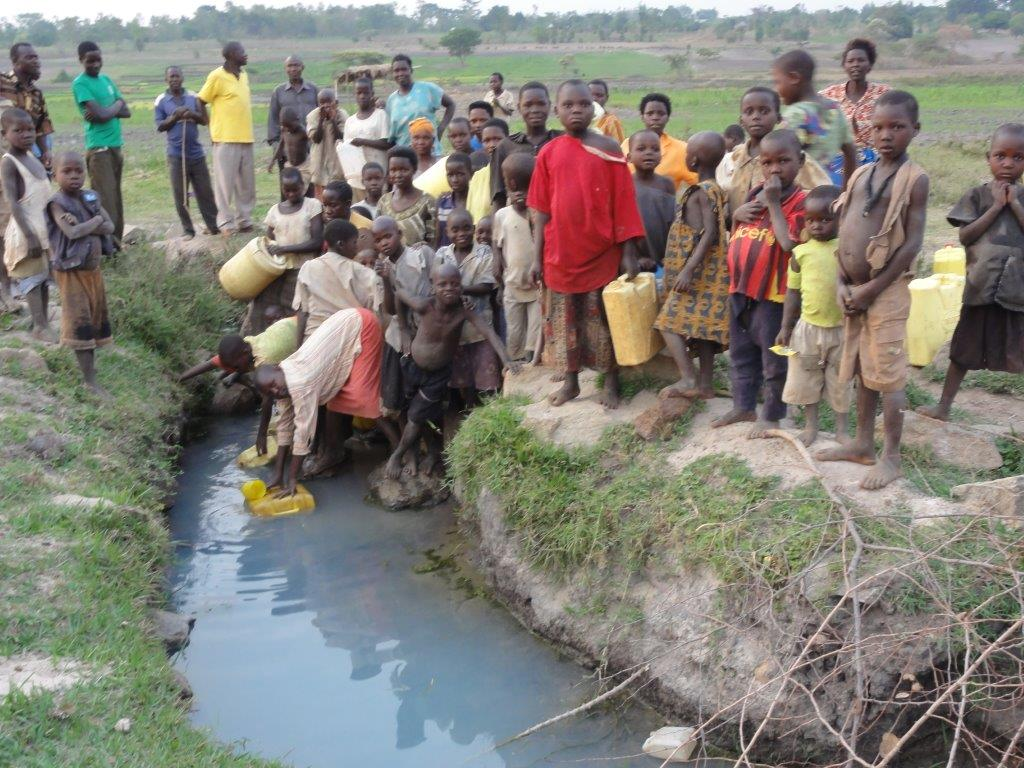 Children filling their containers from a contaminated water source